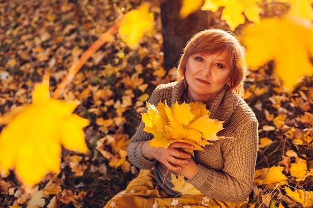 カエデの葉の花束を持っている中年女性。秋の自然を楽しんで、地面に座ってリラックスする女性