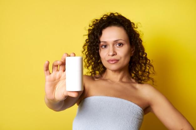 Женщина средних лет держит бутылку косметического продукта, изолированную на желтом фоне