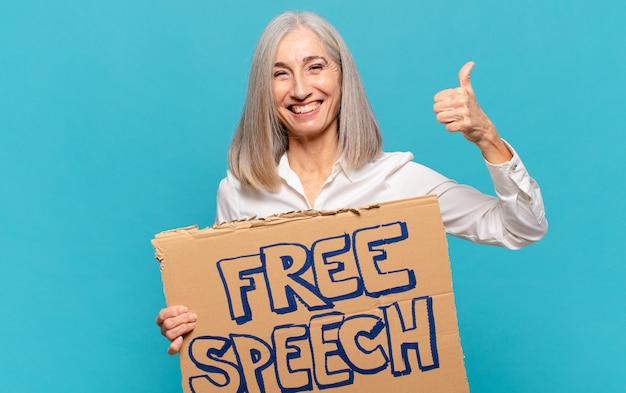 Женщина средних лет держит доску свободы слова и бросает палец вверх