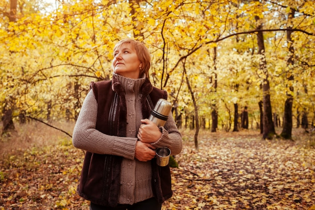 Middle-aged woman holding thermos and cups for drinking tea in autumn forest
