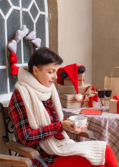Женщина среднего возраста держит чашки чая или кофе
