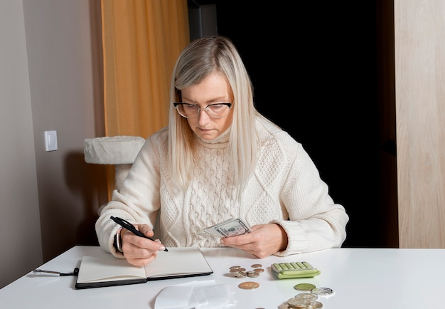Женщина средних лет держит в руках денежные долларовые банкноты и делает запись в блокноте-планировщике
