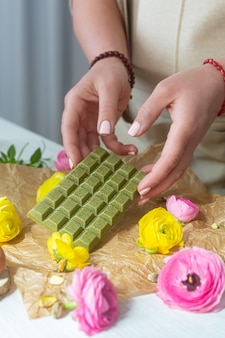 Middle aged woman holds organic matcha green chocolate with natural ingredients