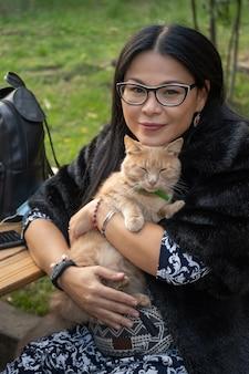 中年女性は屋外のベンチで休んでいる間猫を抱きしめます。黒で幸せな金持ちのアジアの女性