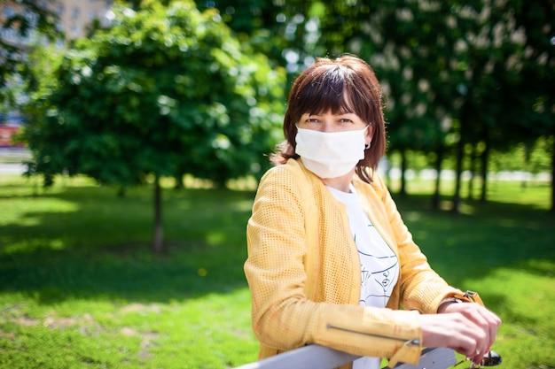 Женщина средних лет в защитной белой маске гуляет в парке в солнечный весенний теплый день
