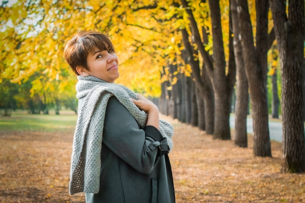 스카프를 두른 중년 여성이 가을 공원을 산책합니다. 오렌지 잎. 활동적인 라이프 스타일