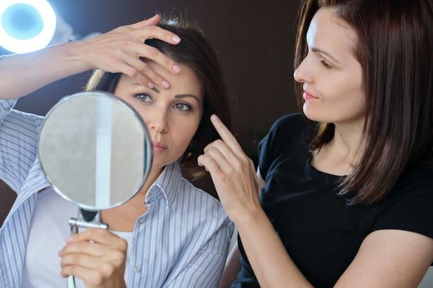 Среднего возраста женщина в салоне красоты, разговаривает с косметологом и смотрит в зеркало