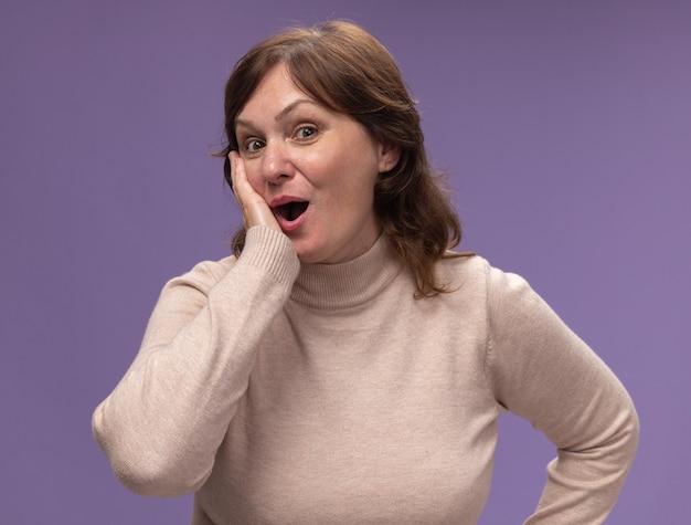 베이지 색 터틀넥의 중간 세 여자는 보라색 벽 위에 서서 놀랐고 놀랐습니다.