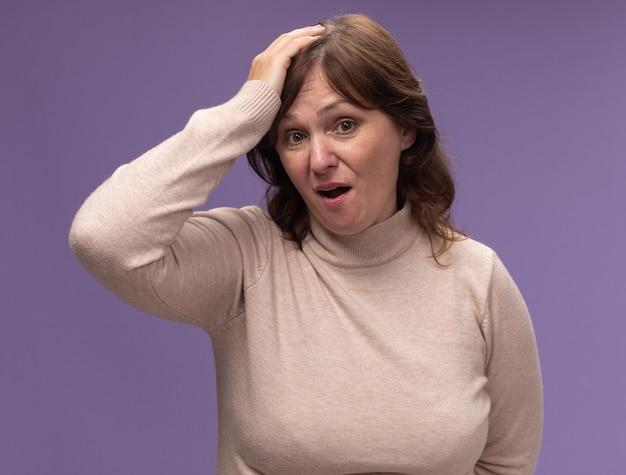 ベージュのタートルネックの中年女性は、紫色の壁の上に立っている間違いのために彼女の頭に手を置いて混乱し、非常に心配しています