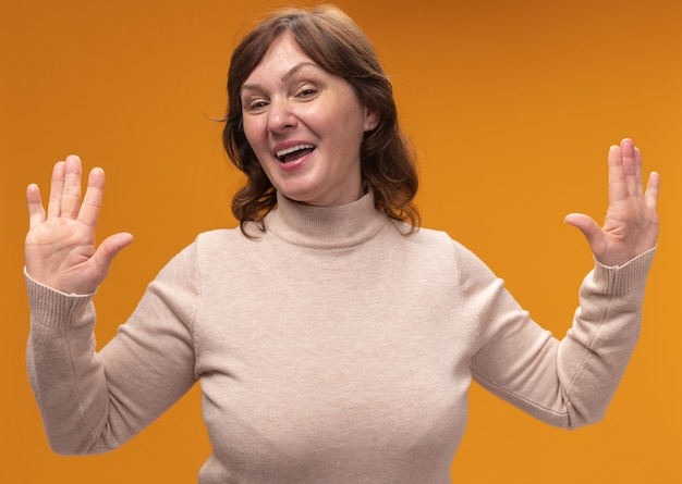 オレンジ色の壁の上に立って降伏で手のひらを上げるベージュのタートルネックで幸せで陽気な笑顔の中年女性