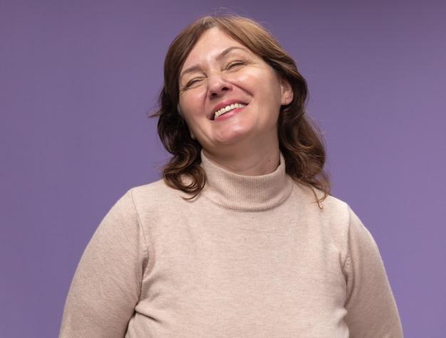 Женщина средних лет в бежевой водолазке счастлива и весело улыбается с закрытыми глазами, стоя над фиолетовой стеной