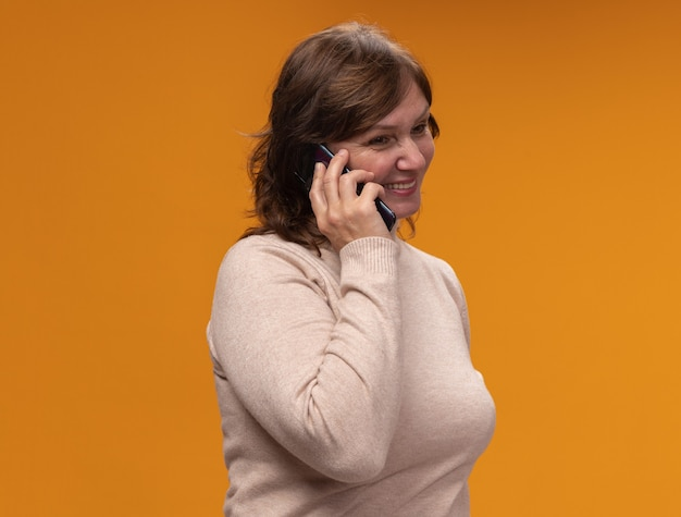 オレンジ色の壁の上に立っている携帯電話で話している間、ベージュのタートルネックで幸せで前向きな笑顔の中年女性