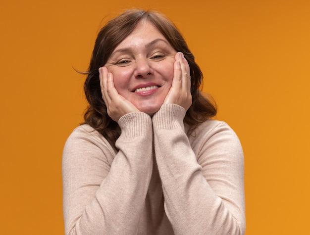オレンジ色の壁の上に立って笑っている彼女の頬に腕を持って幸せでポジティブなベージュのタートルネックの中年女性