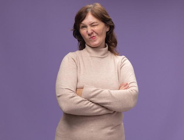 베이지 색 터틀넥에 중간 나이 든 여자 팔을 회의적인 표정으로 옆으로 찾고 보라색 벽 위에 서 교차