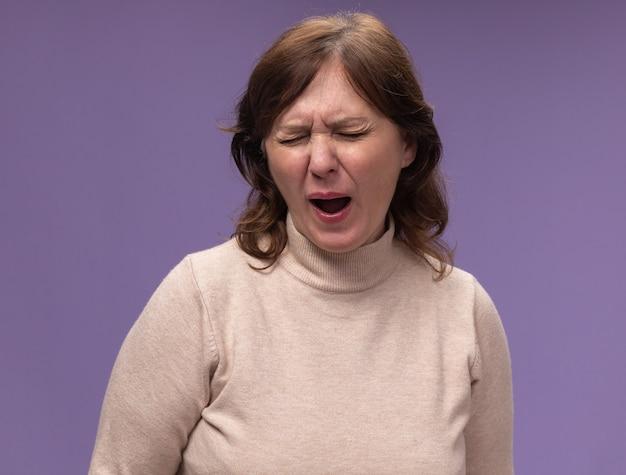 紫の壁の上に立って疲れて退屈なあくびをしているベージュのタートルネックの中年女性
