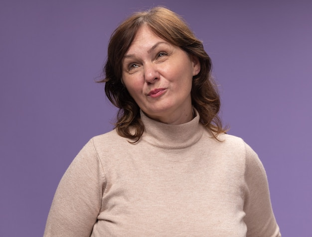 베이지 색 터틀넥에 중간 나이 든 여자가 보라색 벽 위에 서서 불쾌 해하는 것을 찾고 있습니다.