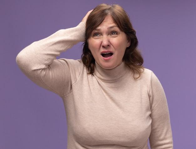 紫色の壁の上に立っている間違いのために彼女の頭に手を置いて混乱し、非常に心配しているベージュのタートルネックの中年女性