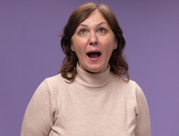 베이지 색 터틀넥에 중간 세 여자는 보라색 벽 위에 행복하고 흥분 서 찾고