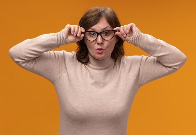 オレンジ色の壁の上に密接に立っている眼鏡をかけているベージュのタートルネックの中年女性