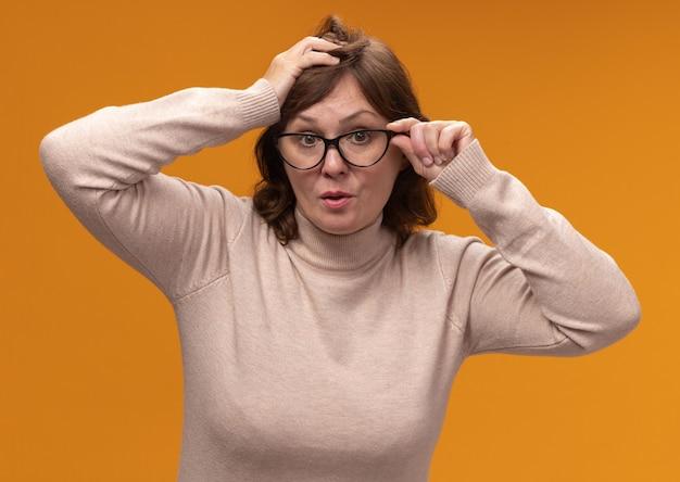 オレンジ色の壁の上に立って驚いた眼鏡をかけているベージュのタートルネックの中年女性