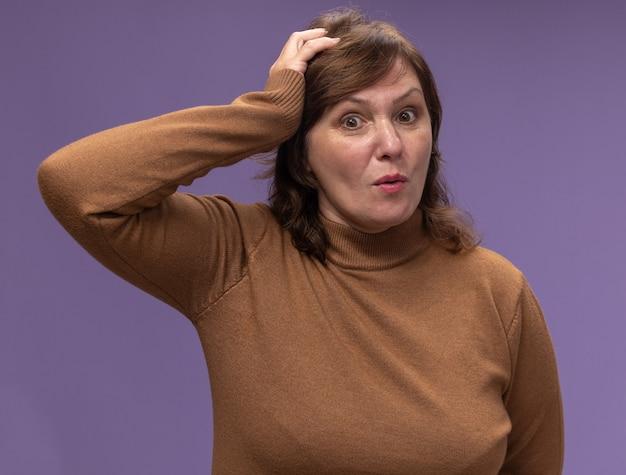 茶色のタートルネックの中年女性は、紫色の壁の上に立っている間違いのために彼女の頭の上の手と混同しました
