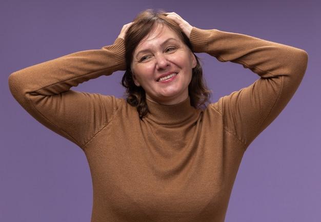 갈색 터틀넥에 중간 세 여자는 보라색 벽 위에 서있는 그녀의 머리에 손으로 옆으로 찾고 행복하고 기쁘게 생각합니다.
