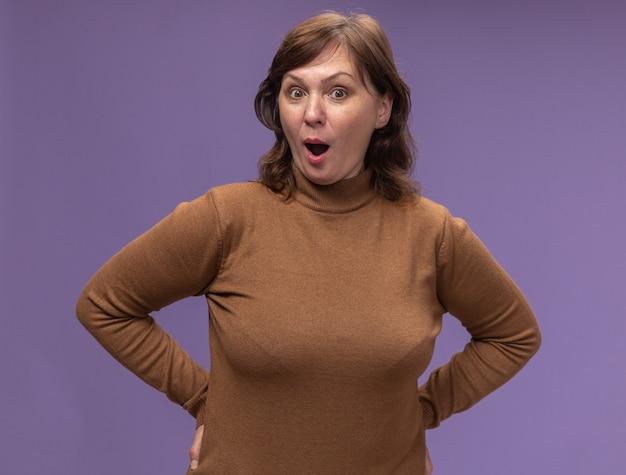 보라색 벽 위에 서있는 갈색 터틀넥에 중간 나이 든된 여자