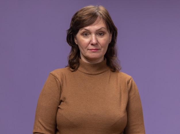 紫色の壁に立っている自信を持って表情と茶色のタートルネックの中年女性