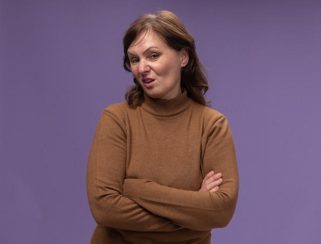 紫色の壁の上に立って腕を組んで懐疑的な表情で茶色のタートルネックの中年女性 無料写真