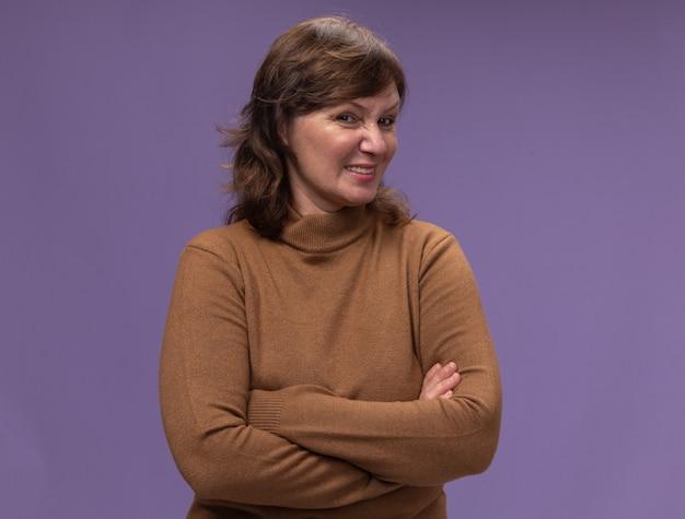 紫色の壁の上に立って腕を組んで懐疑的な表情で茶色のタートルネックの中年女性