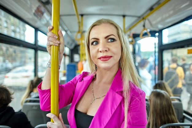분홍색 중간 나이 든 여자는 버스에 서서 손잡이를 잡고있다.