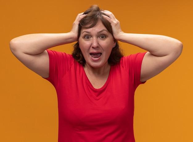 오렌지 벽 위에 서있는 그녀의 머리에 손으로 놀란 빨간 티셔츠에 중간 세 여자
