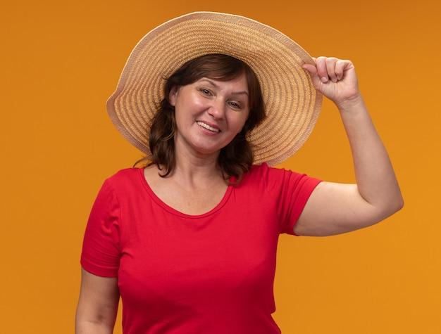 빨간 t- 셔츠와 여름 모자에 중간 세 여자 행복하고 긍정적 인 오렌지 벽 위에 유쾌하게 서 웃고