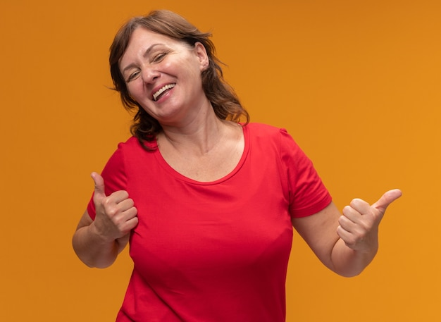 빨간색 티셔츠에 중간 세 여자 행복하고 쾌활한 오렌지 벽 위에 서 엄지 손가락을 보여주는