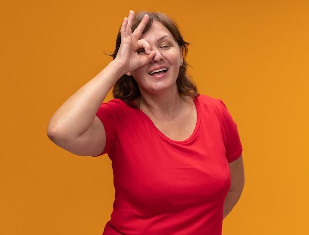 オレンジ色の壁の上に立っているokサインを示す幸せでポジティブな赤いtシャツの中年女性