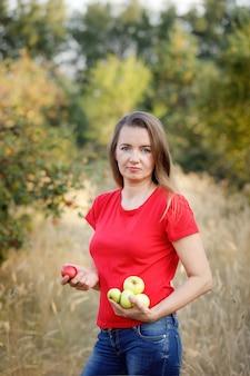庭の緑のリンゴを保持している赤いtシャツの中年の女性