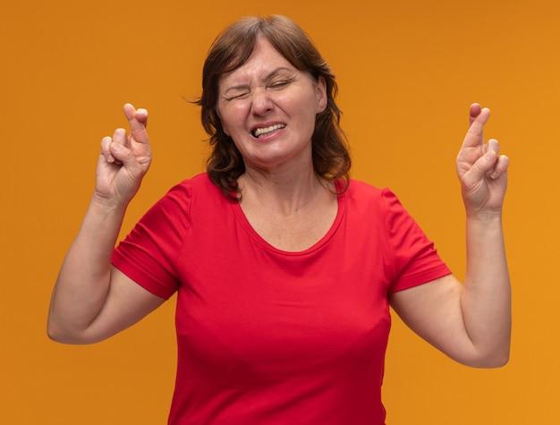Женщина средних лет в красной футболке загадывает желаемое с выражением надежды, скрестив пальцы с закрытыми глазами, стоит над оранжевой стеной