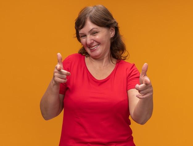 オレンジ色の壁の上に立って幸せで陽気な人差し指で指している赤いtシャツの中年女性