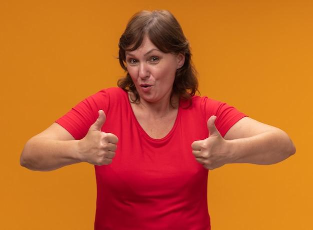 오렌지 벽 위에 서 엄지 손가락을 보여주는 웃 고 빨간 티셔츠에 중간 세 여자