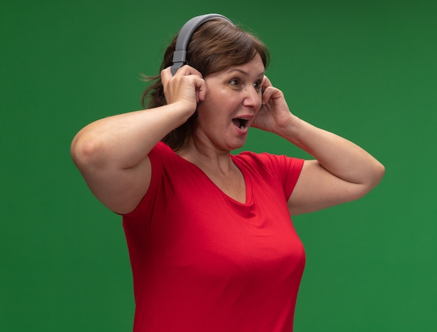 녹색 벽 위에 행복하고 놀란 서 제쳐두고 찾고 헤드폰 빨간색 티셔츠에 중간 세 여자
