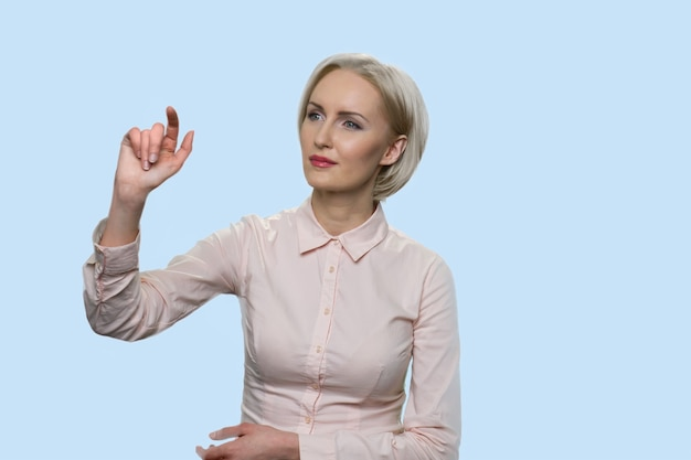 Middle-aged woman is pressing invisible touchscreen. blonde woman in formal clothes isolated on blue background.