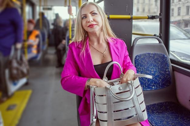 중년 여성은 무릎에 가방을 들고 대중 교통에 앉아 있습니다.