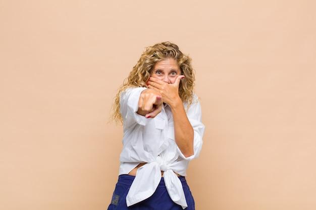 中年の女性があなたを笑い、正面を指して、あなたをからかったり、あざけったりします