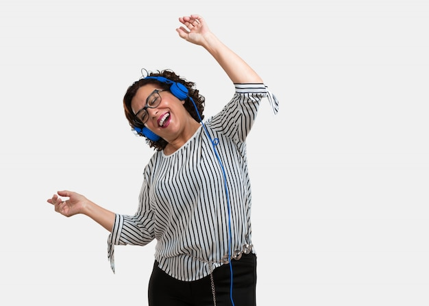 Middle aged woman listening to music, dancing and having fun, moving