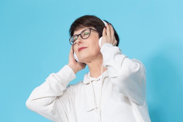 青い背景で音楽を聞いている中年女性