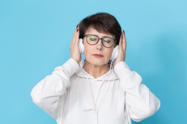 青い壁で音楽を聴いている中年女性。 。