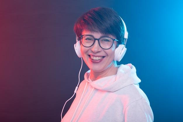コピースペースのあるカラフルな壁で音楽を聴く中年女性。