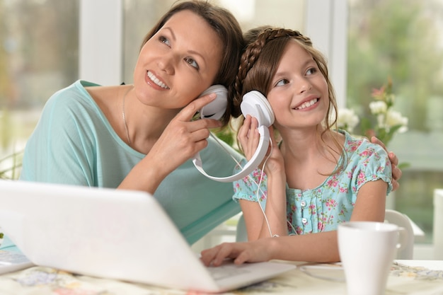 Middle-aged woman and little girl listening music using laptop