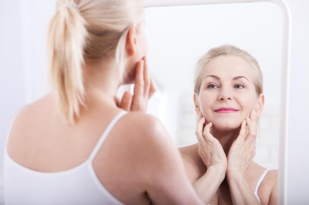 거울에 주름을보고 중간 나이 든된 여자. 선택적 초점