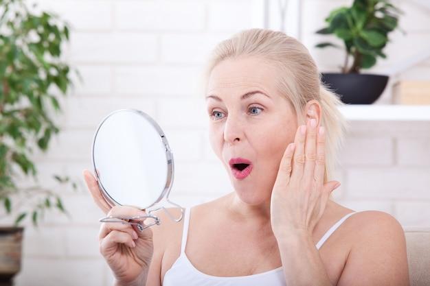 鏡の中のしわを見ている中年女性。セレクティブフォーカス